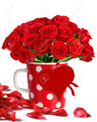 12 red roses in a coffee mug with red heart and rose petals