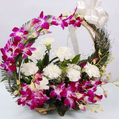 5 orchids with 6 carnations in basket and handle arrangement