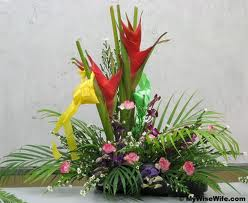Arrangement of bird of paradise with roses and palm leaves