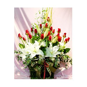 white lilies and red roses in a basket